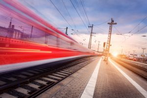 High speed red passenger train on railroad track in motion at beautiful sunset. Blurred commuter train. Railway station in the evening. Railroad travel, railway tourism. Industrial landscape. Train – © den-belitsky - Fotolia.com