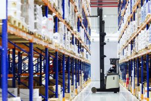 Warehouse worker on forklift pulls boxes from the top shelves in large, modern warehouse – © Petinovs - Fotolia.com