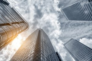 Perspective and underside angle view modern glass building skyscrapers over cloudy sky – © rcfotostock - Fotolia.com